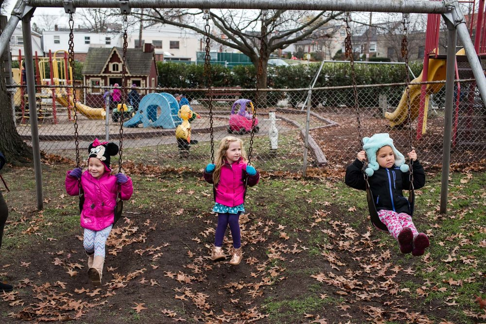 Kids swinging on the swings at nursery school.