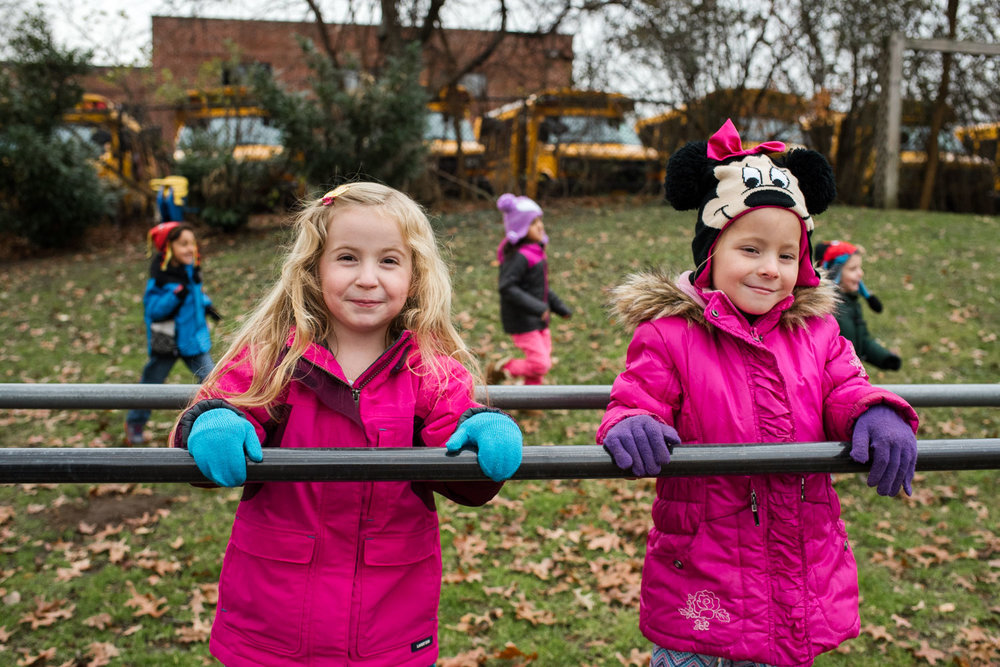Two girls playing on the playground at nursery school.