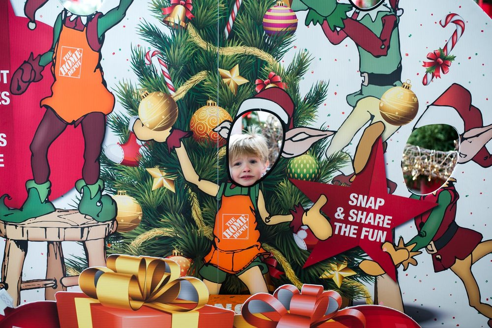 Little boy sticks his head through a Home Depot Christmas display.