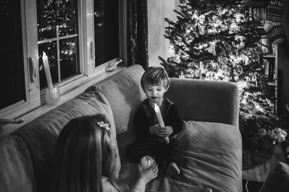 Brother and sister sitting on couch in front of Christmas tree.
