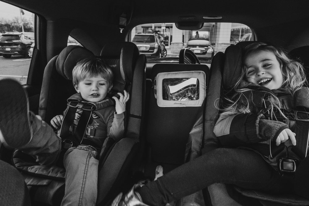 Kids laughing in the backseat of the car.