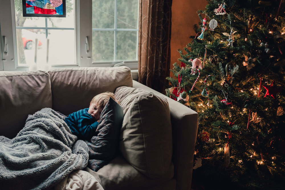 Little boy lying on couch with a blanket next to the Christmas tree.