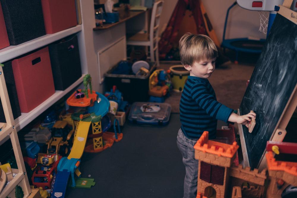 Little boy erasing a chalkboard in playroom.