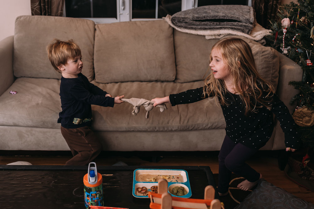 Kids playing tug of war with a toy.