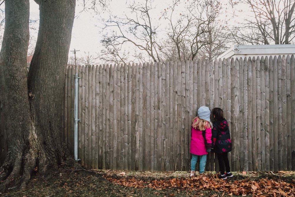 Little girls peeking through a fence.