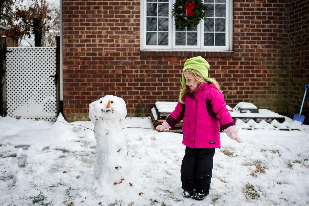 A little girl building a snowman.