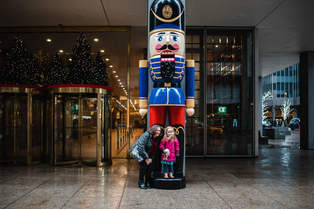 Grandmother and little girl smiling in front of a huge nutcracker.