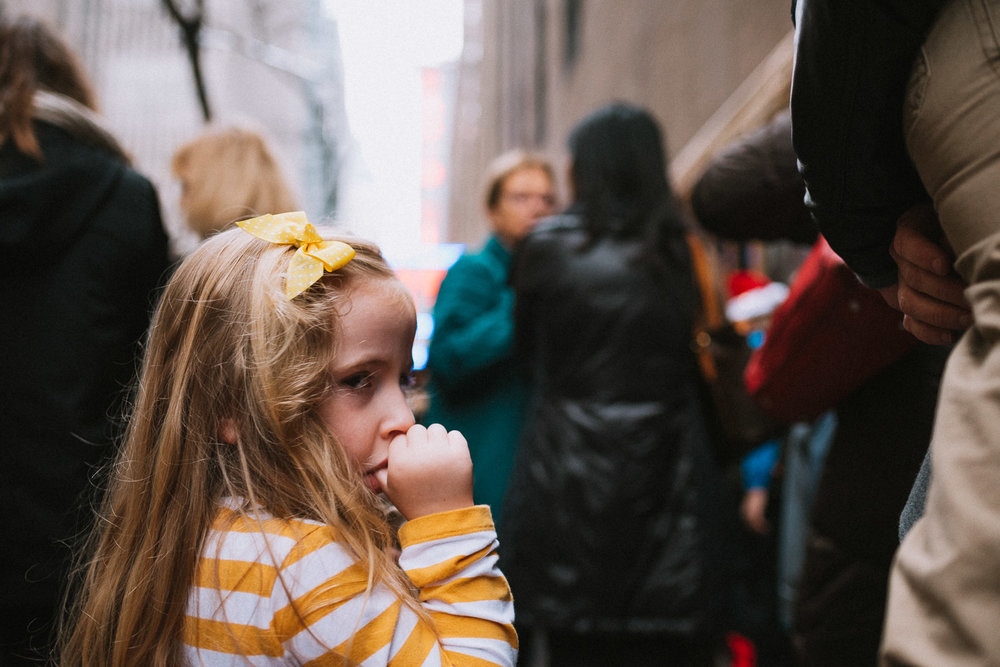 Little girl sucking her thumb while waiting in line.