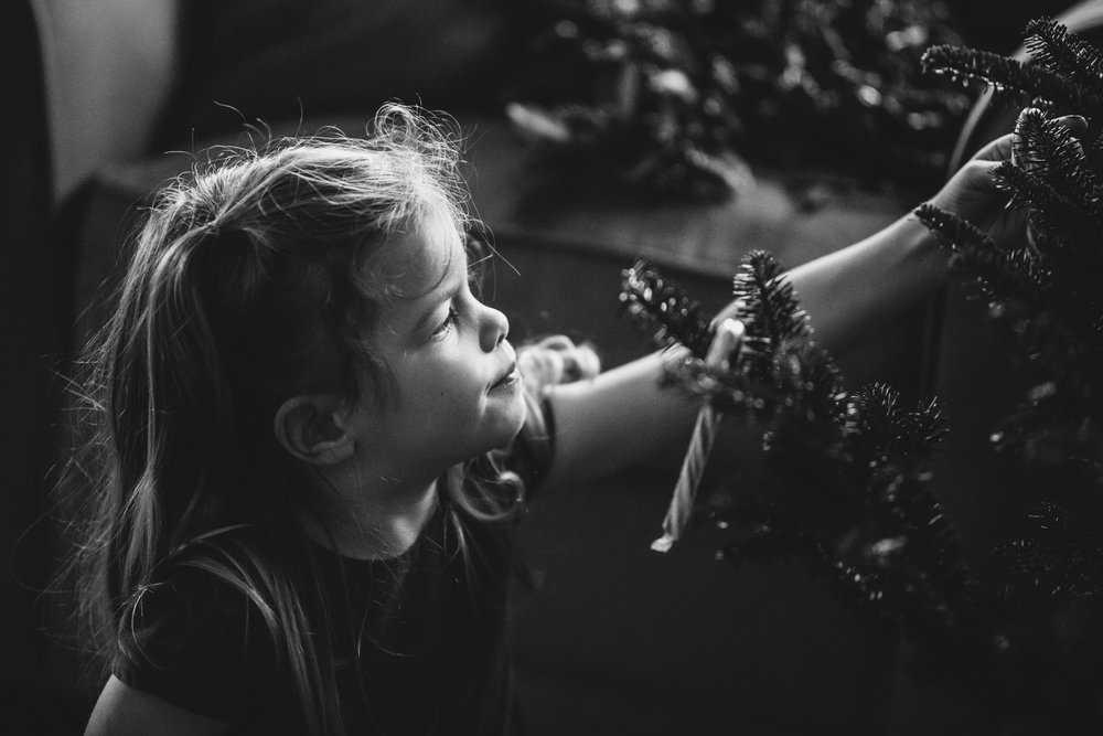 Little girl decorating the Christmas tree.
