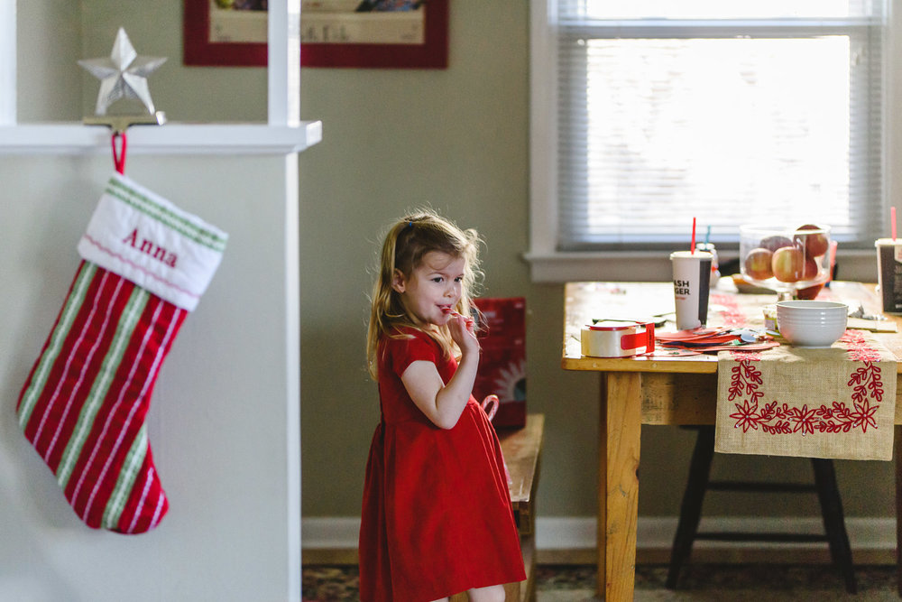 Little girl walking by a Christmas stocking with her name on it.