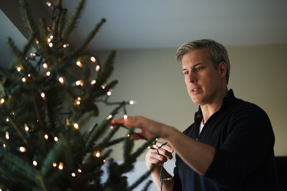 Man decorating a Christmas tree.