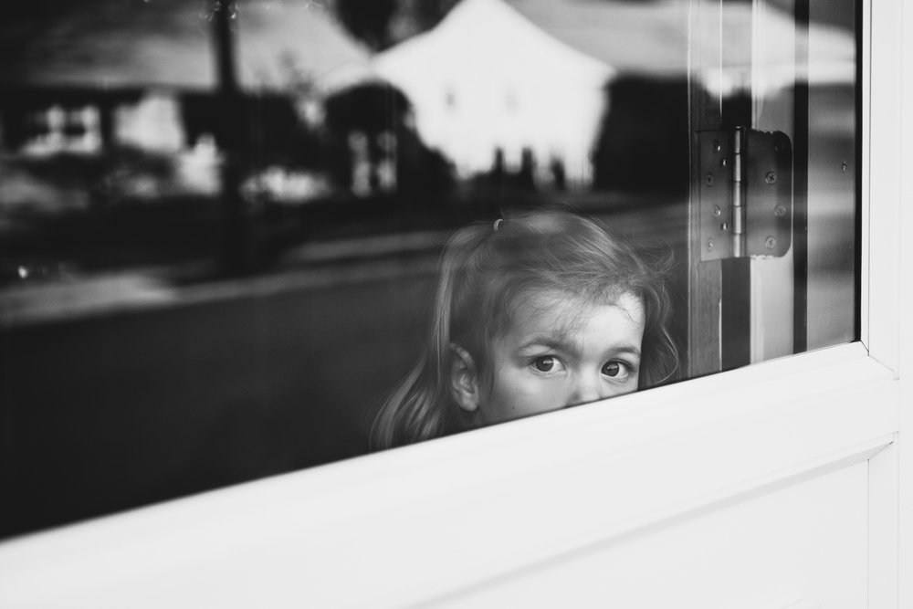 Little girl peering out front door.