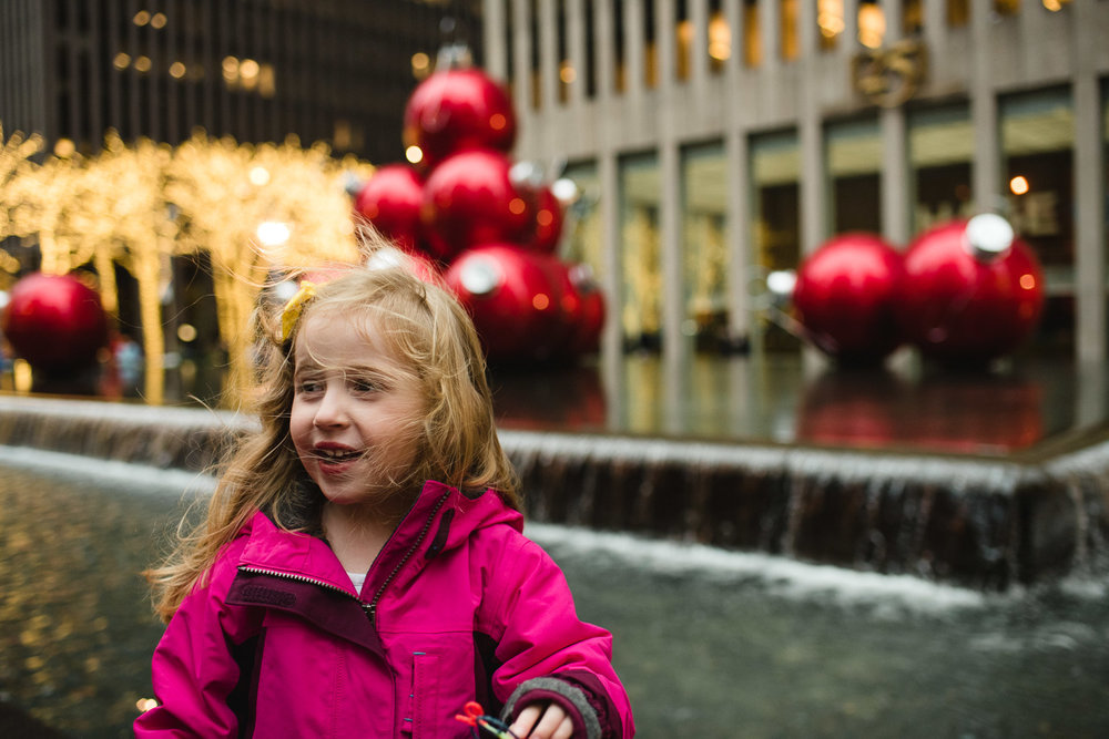 Little girl stands in front of holiday decorations in New York City.