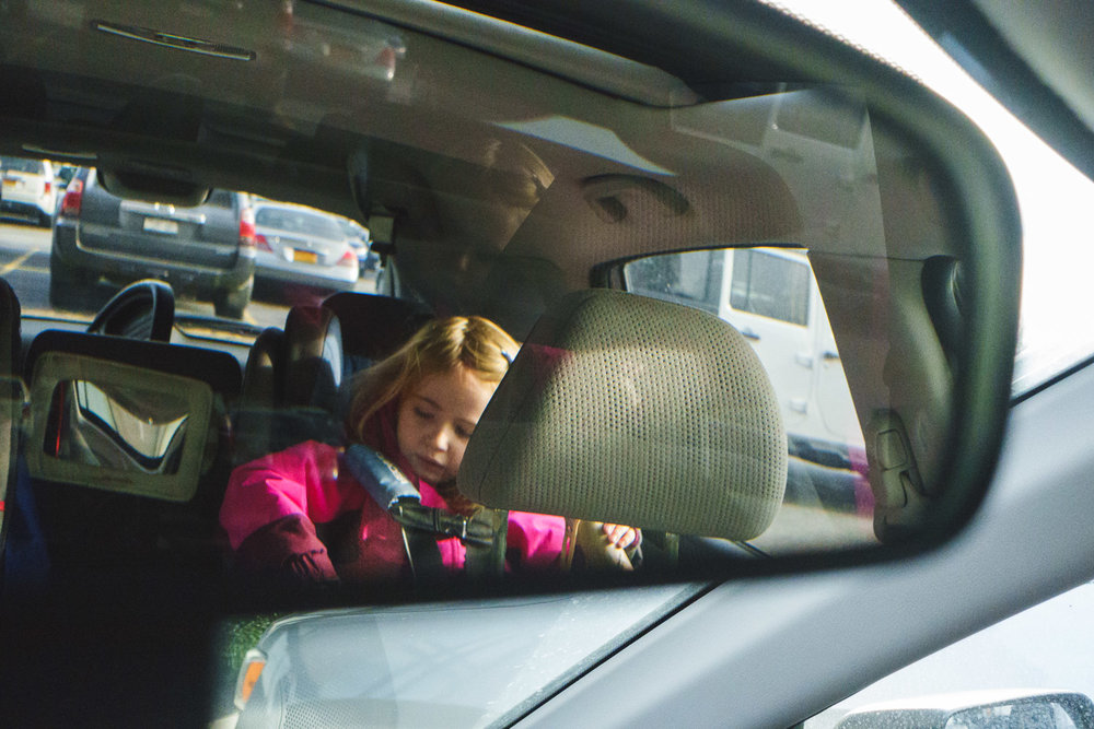 Little girl in rearview mirror.