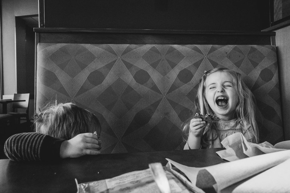 Little girl laughing in a booth at Panera Bread.