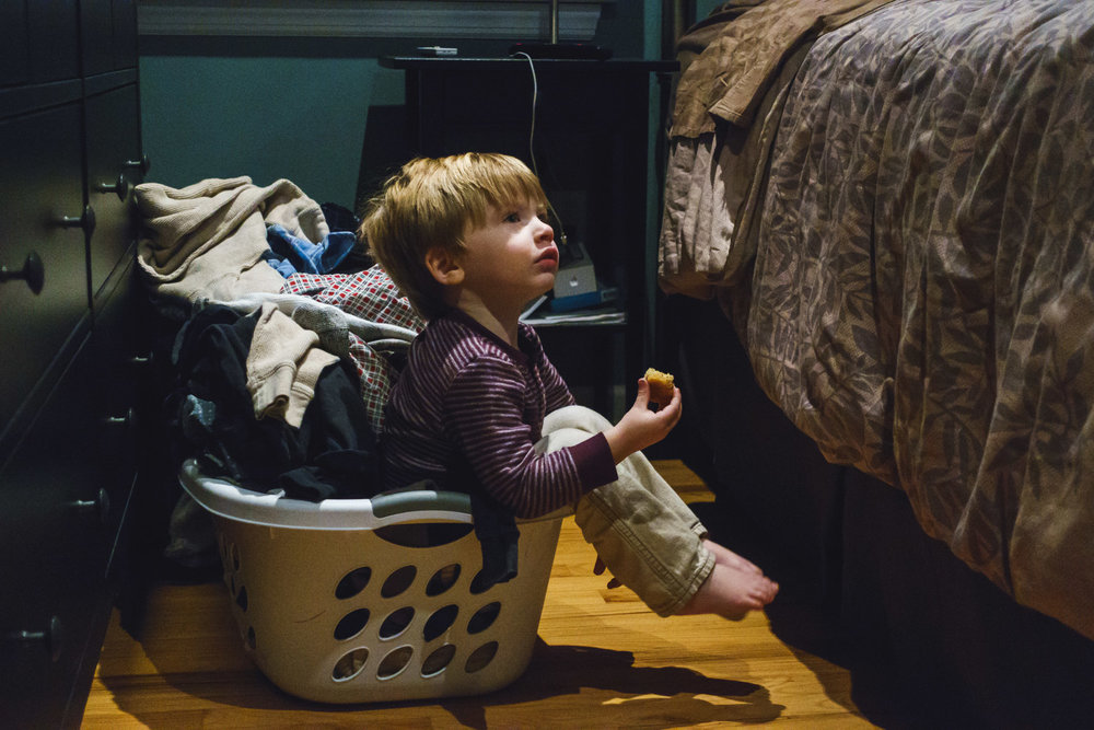 Little boy sitting in a laundry basket full of clothes.