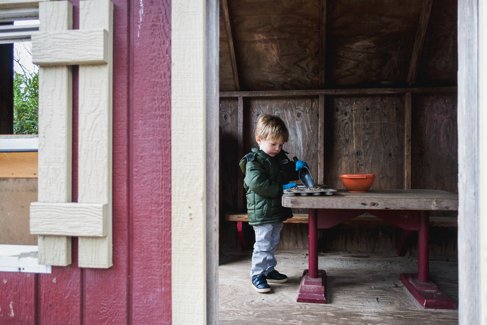 Little boy playing in outdoor playhouse.