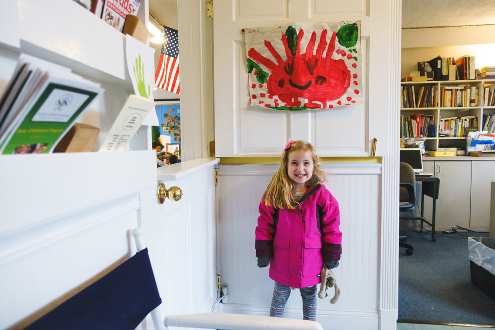 Lila posing outside her classroom under a painting she made.