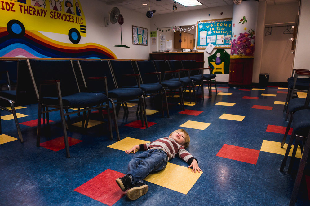 Little boy lying on the floor of speech therapy office.