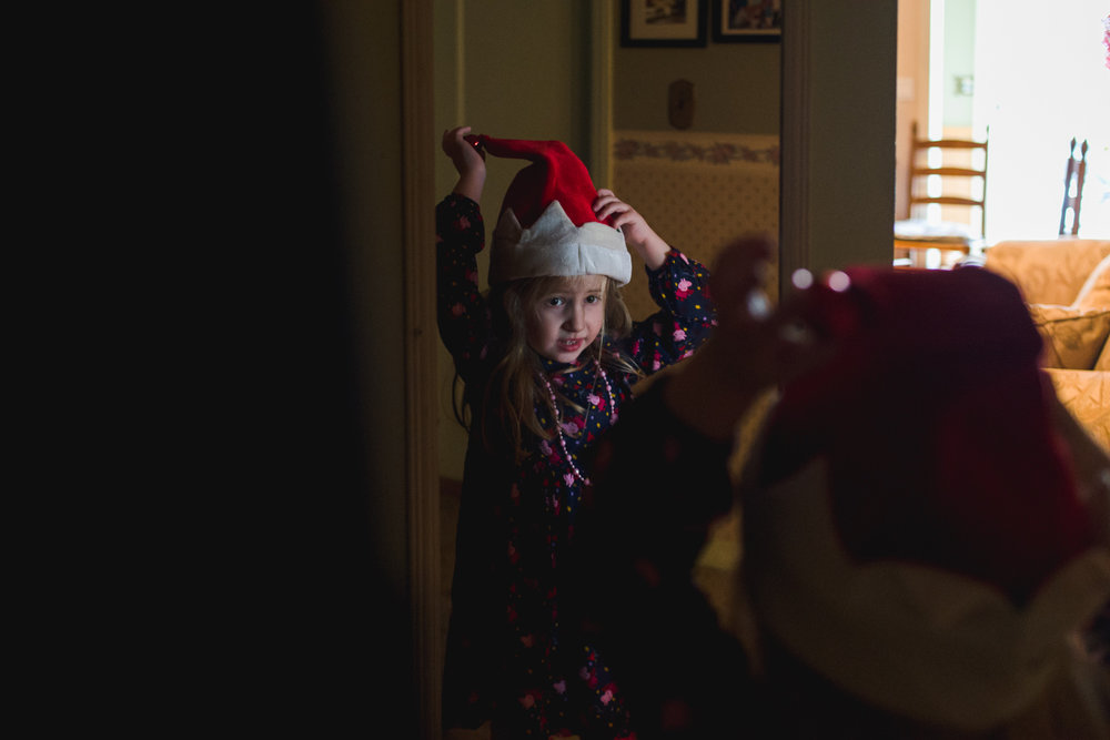 Little girl putting on a Santa hat.