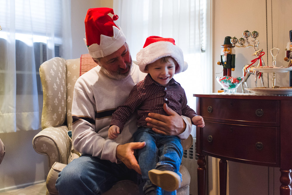 Grandfather and grandson in Santa hats.