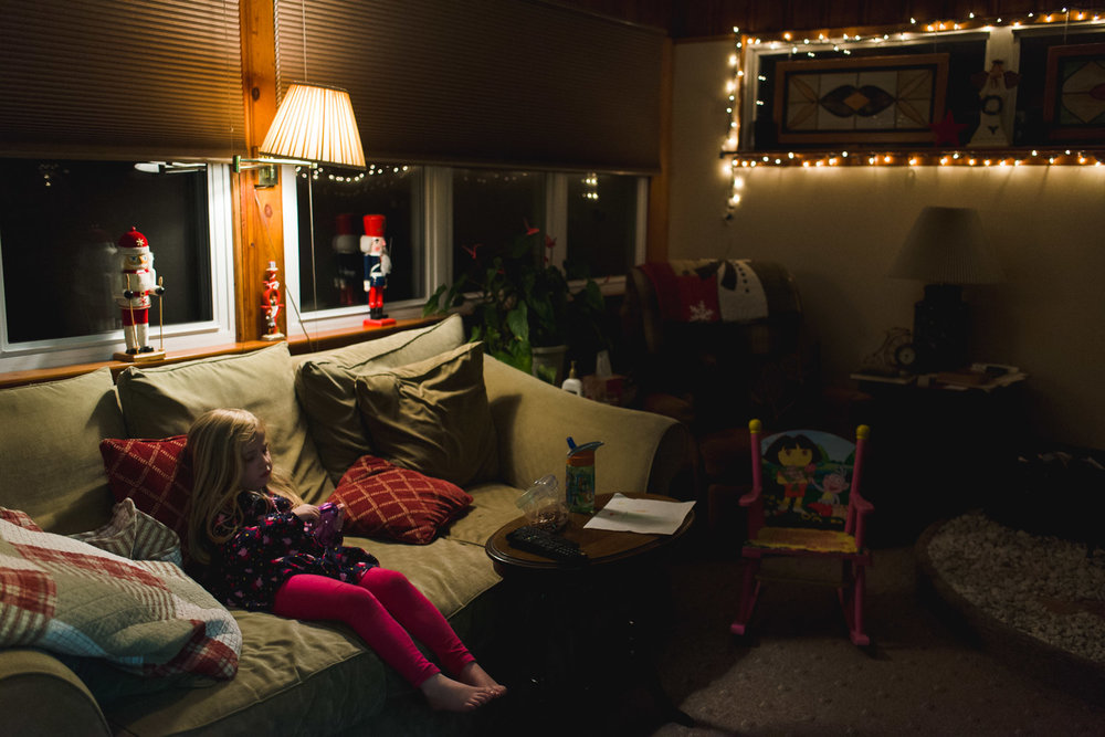 Little girl watching tv in dark living room.