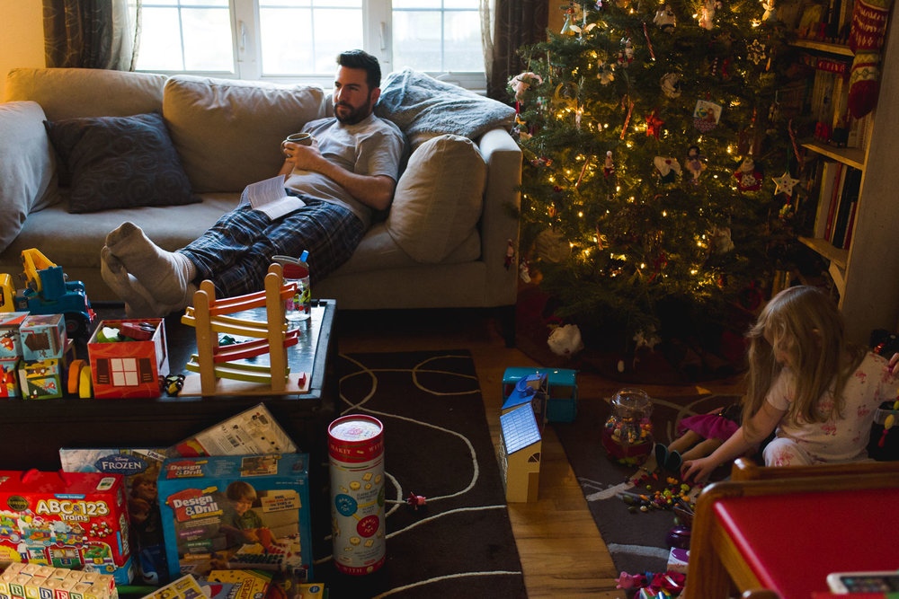 Father and daughter in the living room on Christmas morning.