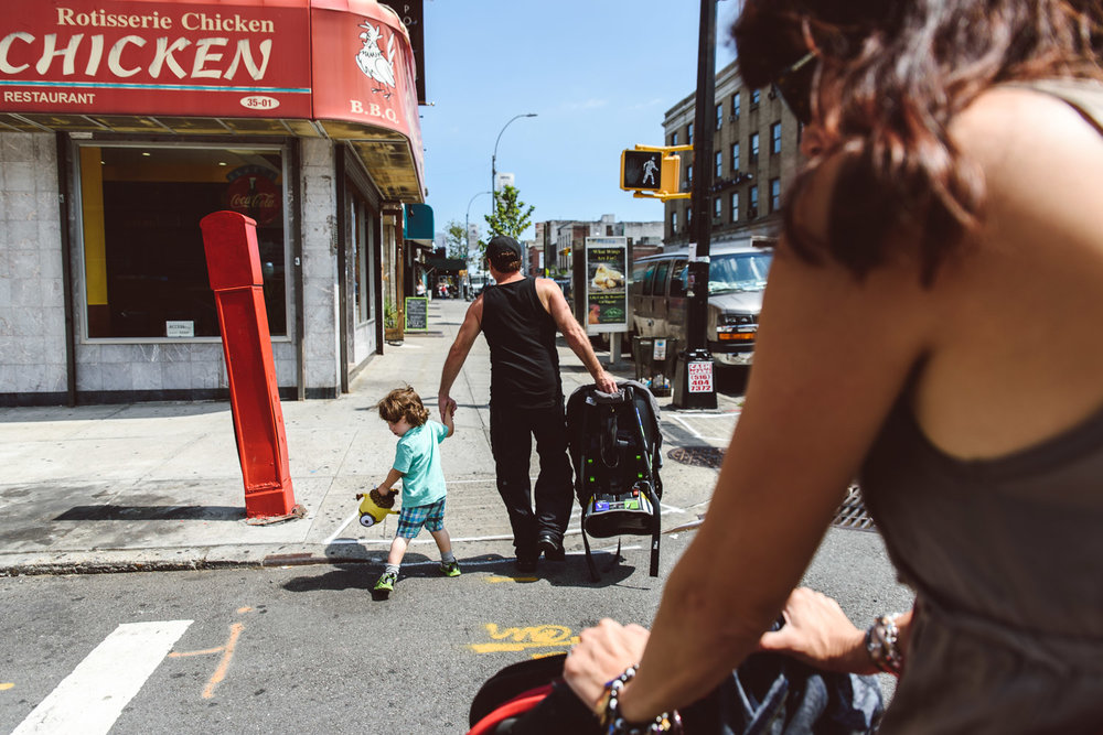 A family crosses the street in Queens, NY.