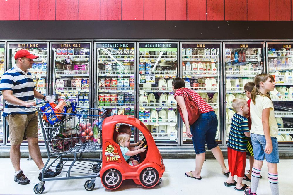 A big family shops in the dairy department of the grocery store.