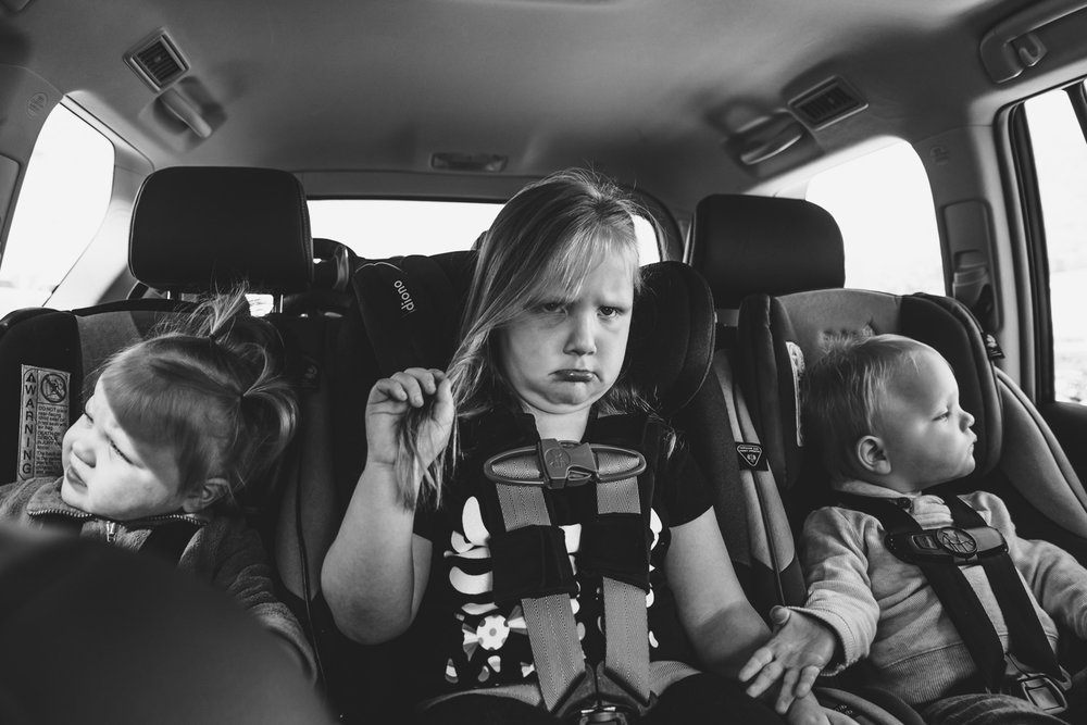 Grumpy preschooler in backseat of car next to baby siblings.
