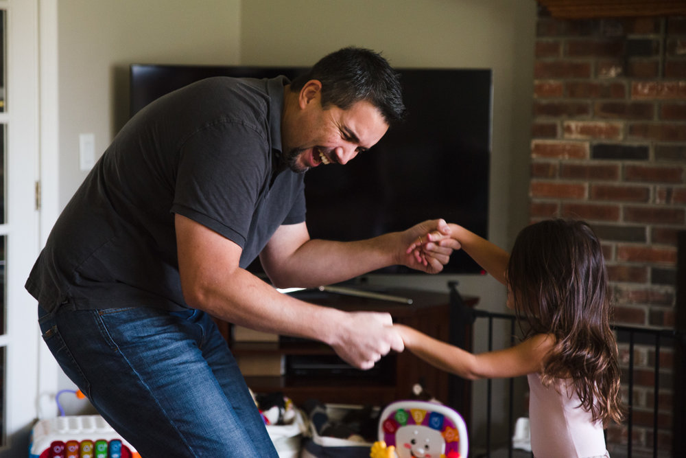Father dances with daughter in living room.