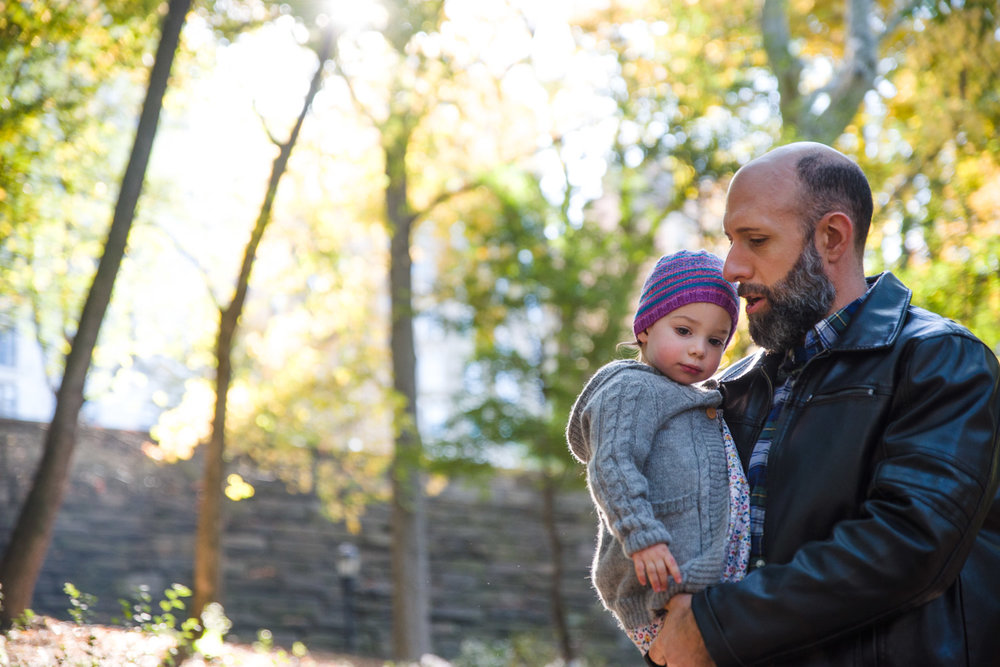 Dad holds toddler daughter in Riverside Park.
