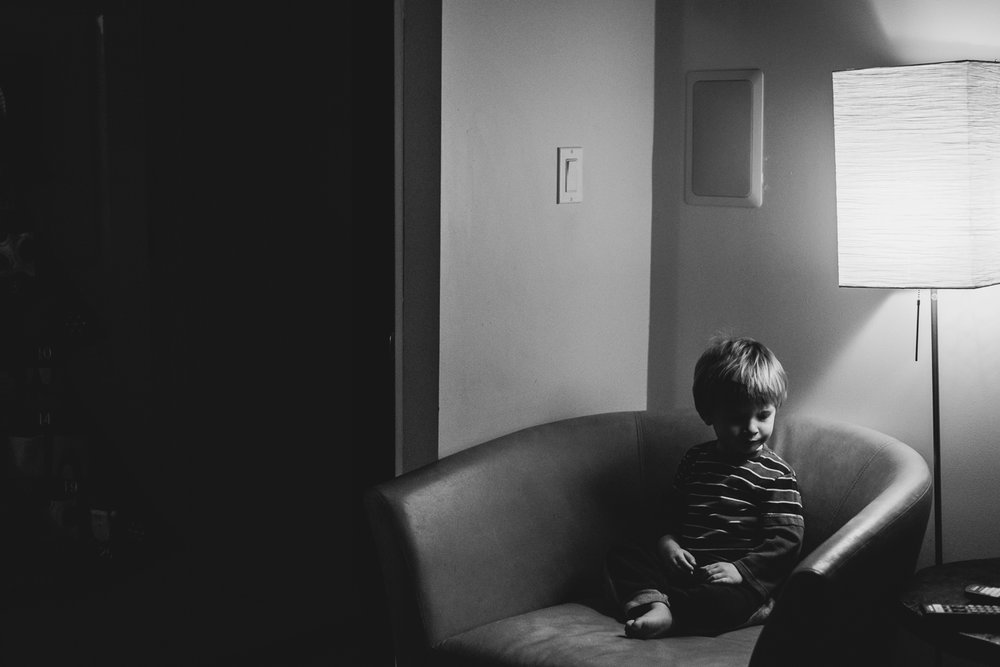 Little boy sitting on a chair under a lamp.
