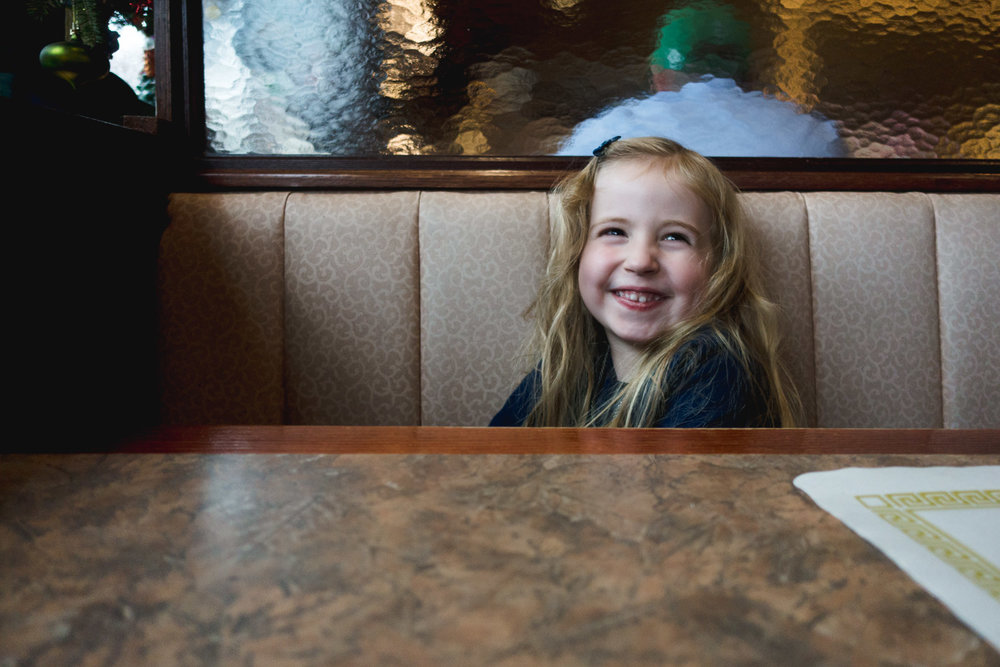 Little girl smiling while sitting in a booth at a diner.