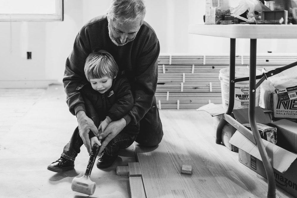 Grandfather helps grandson hammer wood floor in West Hempstead, NY.