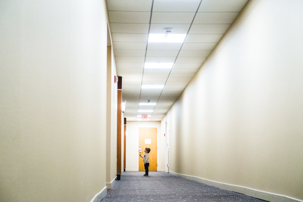 Little boy stands in a long empty hallway.