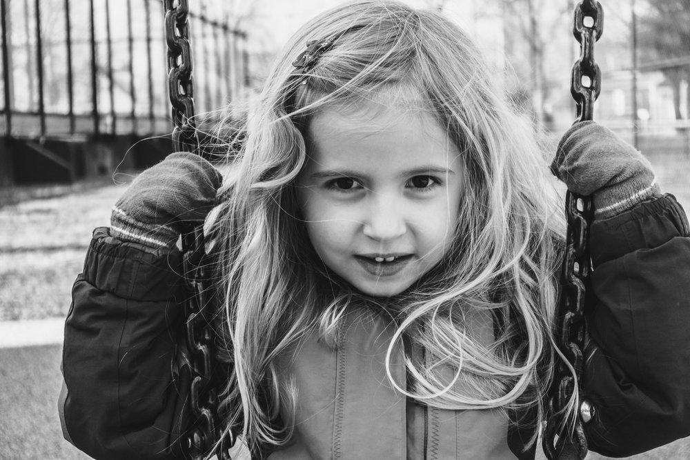 Portrait of a little girl on a swing.