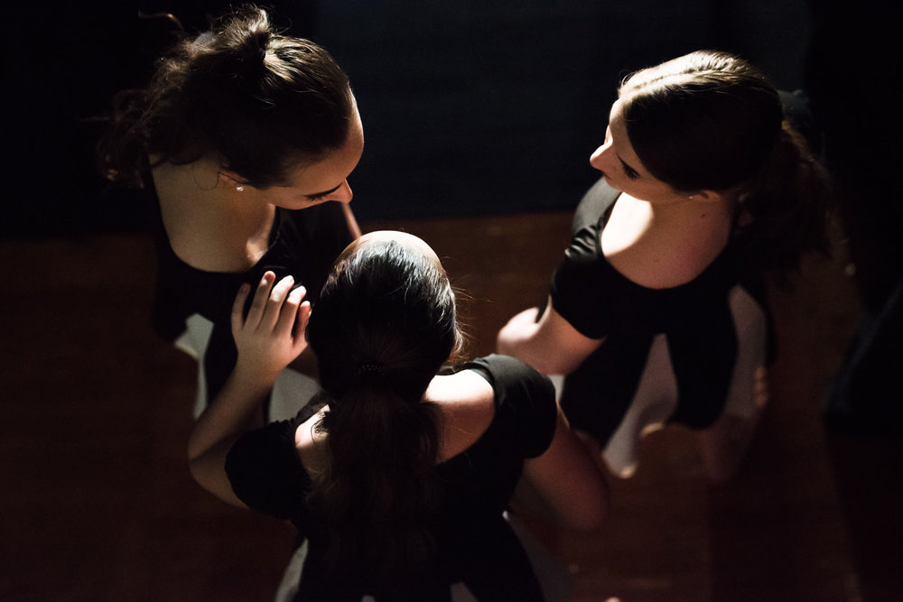 Dancers huddle backstage at Trinity High School.
