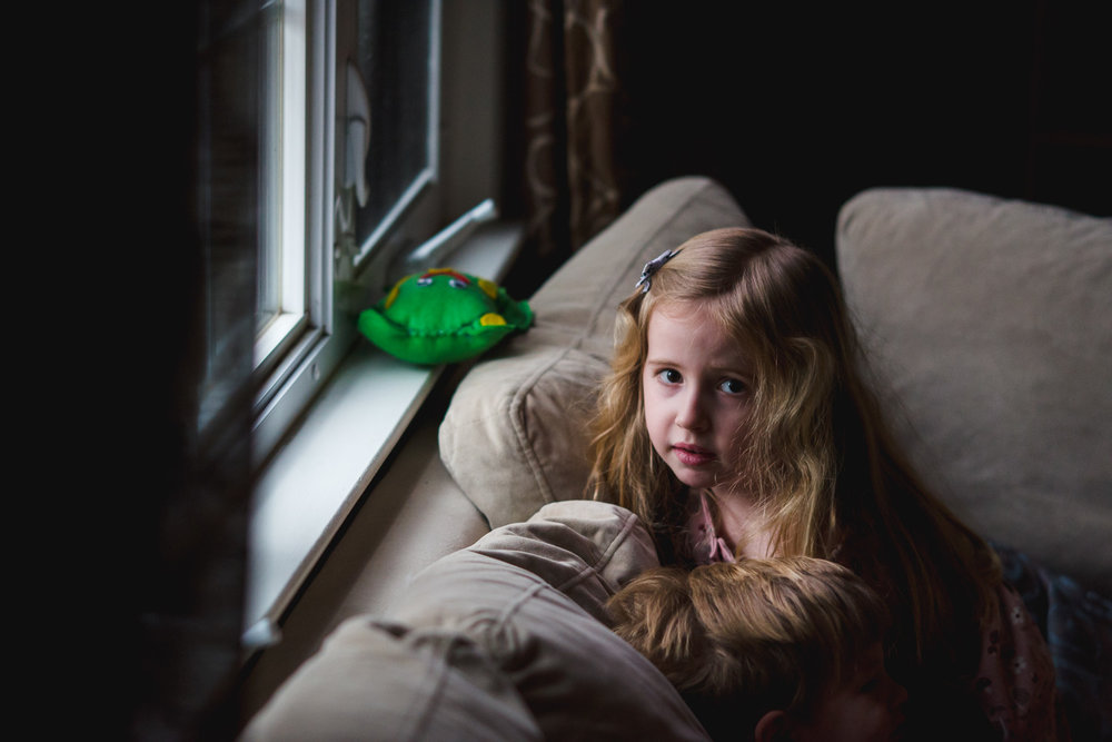 Portrait of a little girl sitting on the couch.