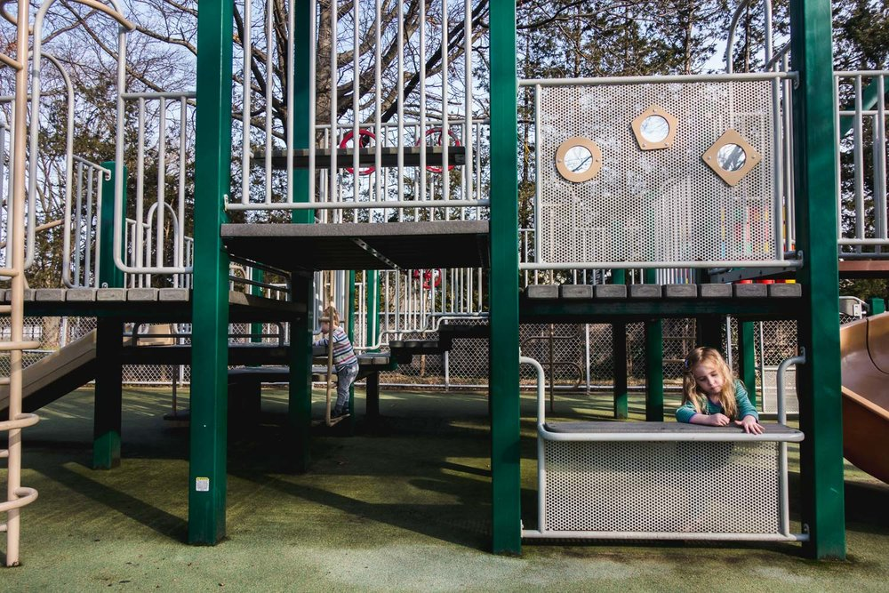 Children play at the playground on a sunny day.