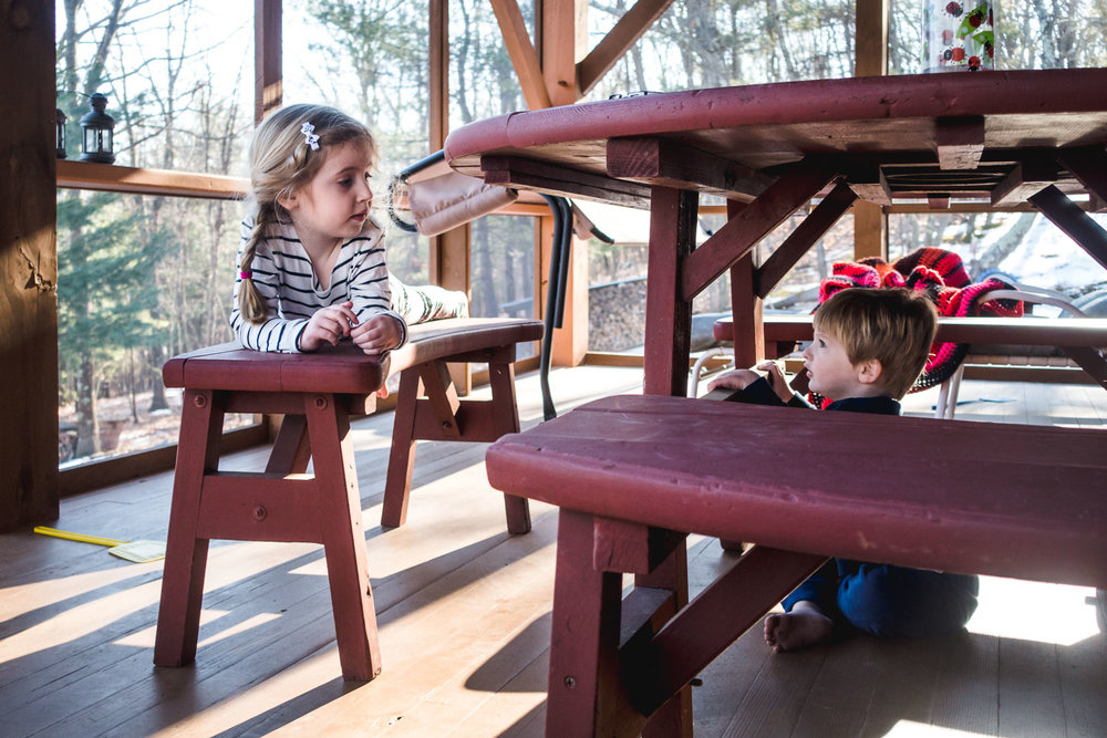 Boy and girl talk to each other under a picnic table.