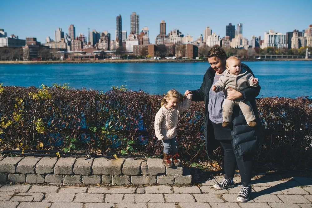 A mother and her children in Socrates Park in front of the NYC skyline.