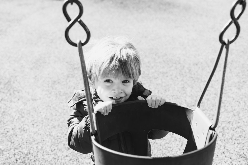 Little boy peers over the top of a swing.