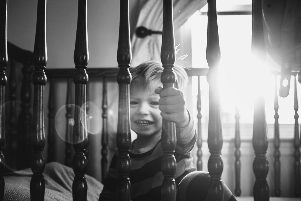 Little boy smiling through his crib slats.