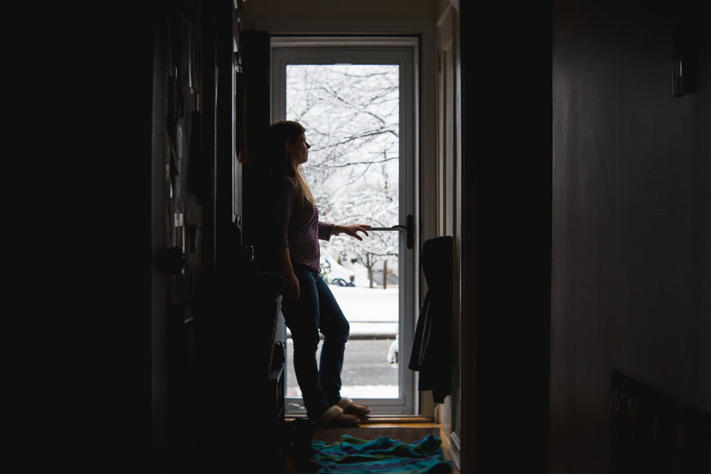 Woman looks out storm door to snowy outdoors.