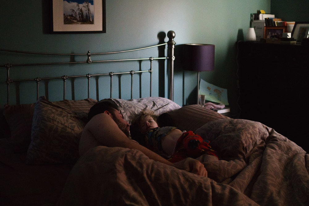 Father and toddler son asleep in bed.