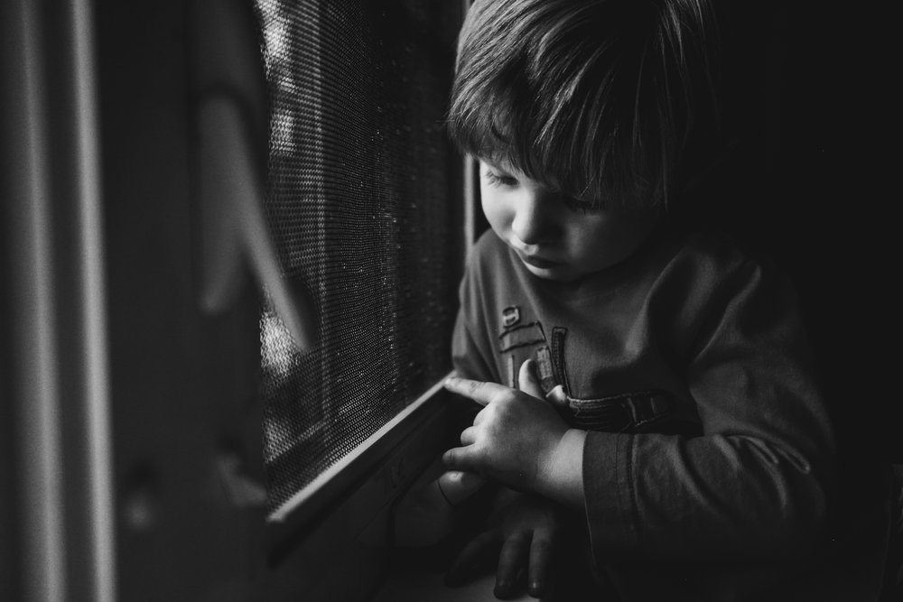A boy looks pensive next to a window.