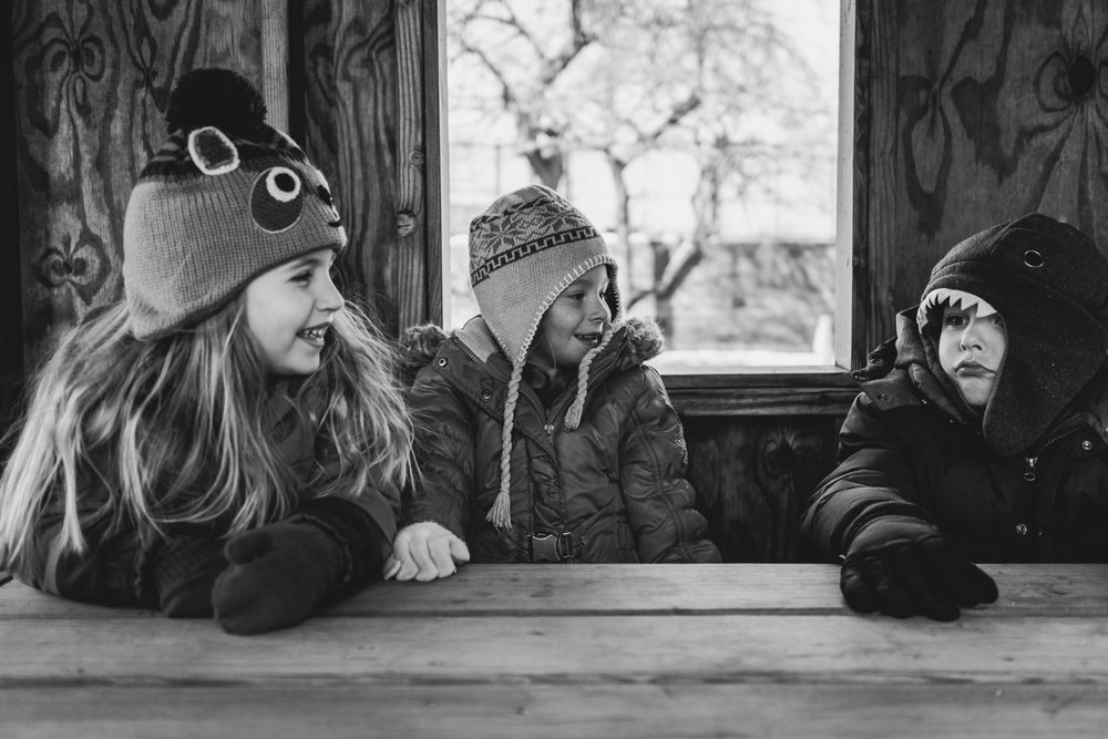 Two girls laugh at a little boy, all dressed in cold weather gear.