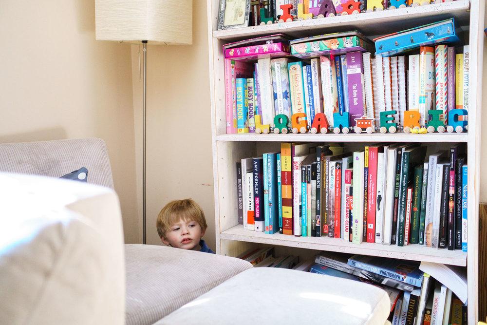 A little boy hides behind a bookcase.
