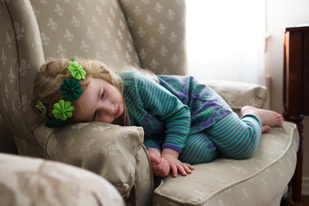 A little girl wearing a shamrock headband lies down in an armchair.